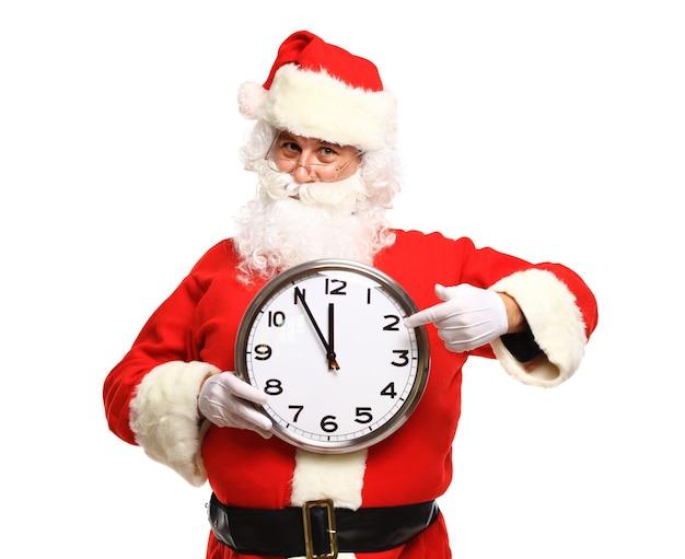 Glücklicher weihnachtsmann in der brille, die auf uhr zeigt, die fünf minuten zu weihnachten zeigt