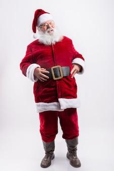 Glücklicher weihnachtsmann, mit den händen im gürtel in der weißen wand