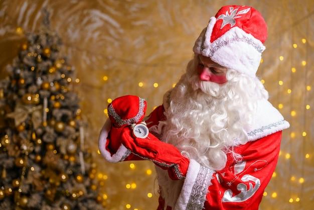 Glücklicher weihnachtsmann mit wecker, der fünf minuten vor mitternacht weihnachtskarte selektiven fokus zeigt