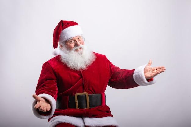 Glücklicher weihnachtsmann, saß mit offenen armen in der weißen wand