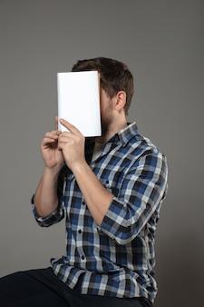 Glücklicher weltbuch- und urheberrechtstag, lesen sie, um jemand anderes zu werden - mann, der das gesicht mit buch bedeckt, während er auf grauer wand liest.