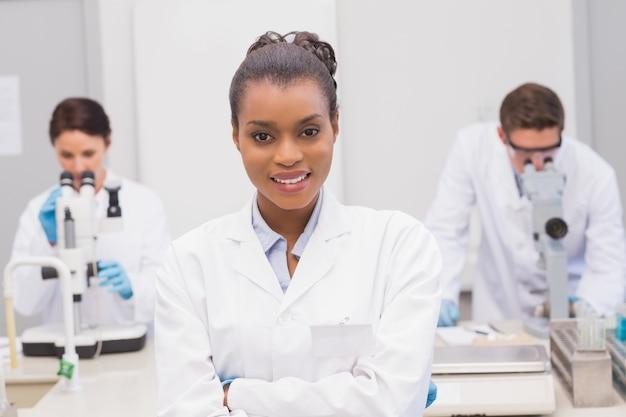 Glücklicher wissenschaftler, der an der kamera mit den armen gekreuzt lächelt