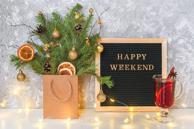 Glücklicher wochenendentext auf brett der schwarzen schrift, festlicher verzierter weihnachtsbaum im handwerkspaket, glas heißer glühwein