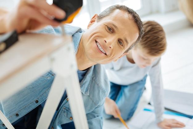 Glücklicher zimmermann. die nahaufnahme eines fröhlichen jungen mannes, der mit hilfe eines maßbandes das tischbein misst und lächelt, während sein sohn die blaupause studiert