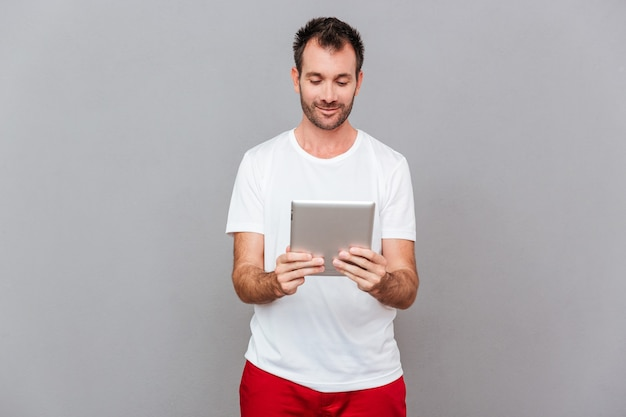 Glücklicher zufälliger mann mit tablet-computer auf grauem hintergrund isoliert