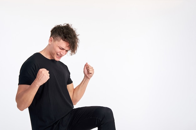 Glücklicher zufriedener junger mann, der einen erfolg feiert und jubelt, der ellbogen wie geste ja gegen weiße wand beugt. positive gefühle.