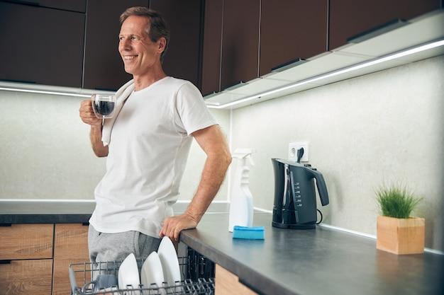 Glücklicher zufriedener reifer mann, der sich auf möbel in der küche stützt und direkt auf das fenster schaut