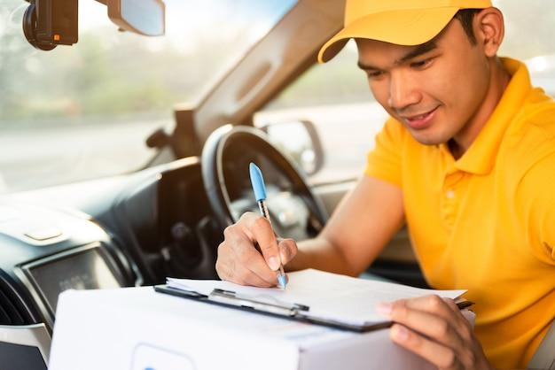 Glücklicher zusteller in der gelben poloshirtuniform mit paketkarton im auto