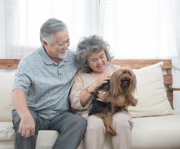 Glückliches älteres älteres asiatisches paar sitzt auf sofa zusammen mit haustiertherapie in der krankenpflegetagesstätte, pensionierter mann und frau, die hund halten, während sie auf couch im wohnzimmer zu hause sitzen.