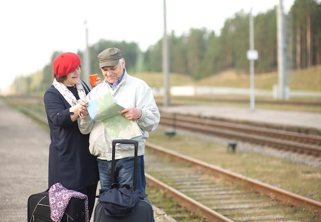 Glückliches älteres älteres ehepaar mit koffern, die auf die karte schauen und auf den zug warten, um eine reise zu gehen