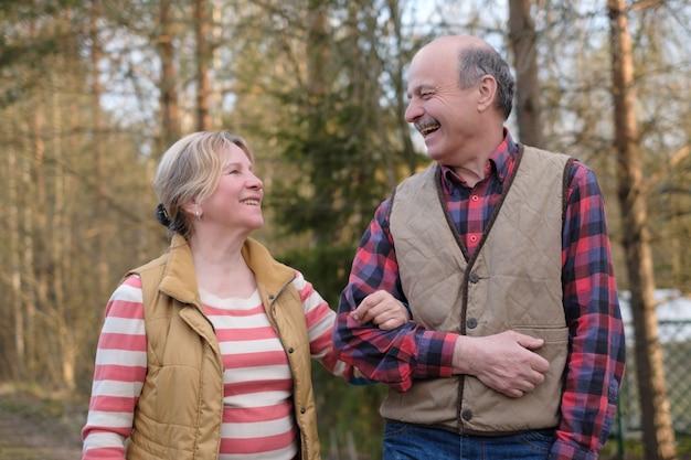 Glückliches älteres älteres paar, das im park geht