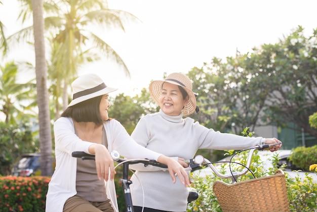Glückliches älteres asiatisches frauenradfahrrad mit tochter am park,