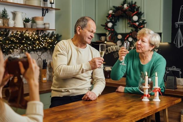 Glückliches älteres ehepaar, das hochzeitstag feiert. 60er jahre glücklicher ruhestand. valentinstag seniorentag. champagner datum. hochwertiges foto