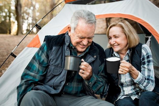 Glückliches älteres ehepaar, das kaffee durch das zelt im wald trinkt