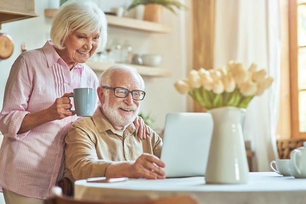 Glückliches älteres ehepaar, das laptop benutzt, während es den morgen zusammen in der küche verbringt?