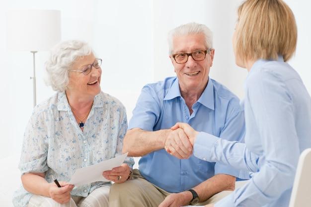Glückliches älteres ehepaar, das mit einem handschlag einen vertrag für den ruhestand besiegelt
