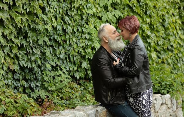 Glückliches älteres ehepaar im ruhestand, das spaß beim küssen hat. liebeskonzept des freudigen älteren und ruhestandslebensstils mit mann, der frau in den augen schön beobachtet.