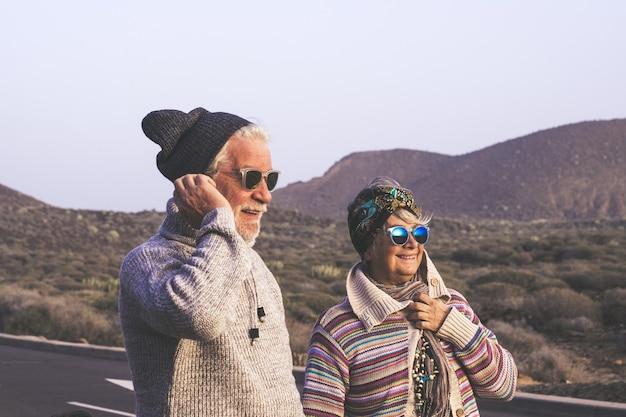 Glückliches älteres ehepaar im ruhestand in warmer kleidung, das eine wandertour genießt. aktive ältere paare, die zusammen gehen und die malerische aussicht während des urlaubs genießen. stilvolles älteres paar, das im freien reist