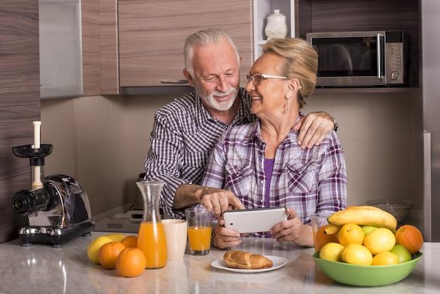 Glückliches älteres kaukasisches paar, das hinter der küchentheke steht