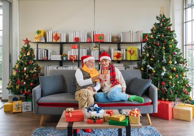 Glückliches älteres kaukasisches paar, das weihnachtsmütze trägt, die auf der sofacouch sitzt und champagnerflöte zusammen zu hause mit verziertem weihnachtsbaum im gemütlichen wohnzimmer hält und anfeuert. silvester feiern.