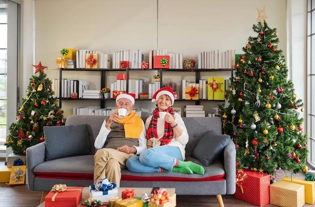 Glückliches älteres kaukasisches paar in weihnachtsmütze, das zusammen auf der sofacouch sitzt und heißes getränk zu hause mit verziertem weihnachtsbaum und geschenken im gemütlichen wohnzimmer hält. urlaub entspannen.