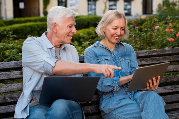 Glückliches älteres paar auf bank im freien mit laptop und tablette
