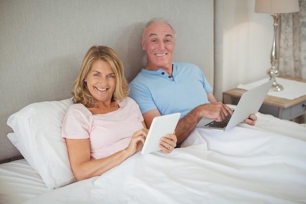 Glückliches älteres paar auf bett mit laptop und digitalem tablet