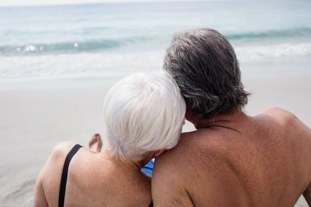 Glückliches älteres paar, das am strand sitzt