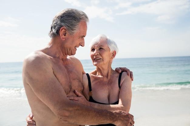 Glückliches älteres paar, das am strand umarmt
