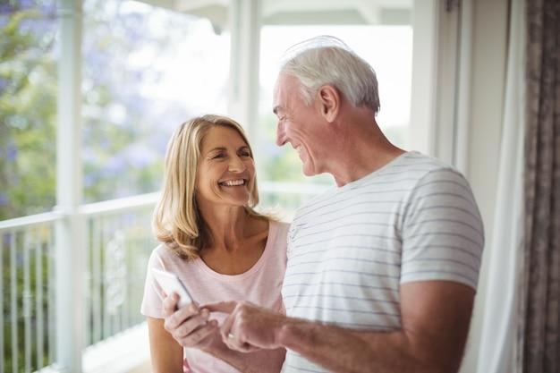 Glückliches älteres paar, das auf balkon miteinander interagiert
