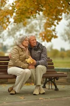 Glückliches älteres paar, das auf bank im herbstpark sitzt