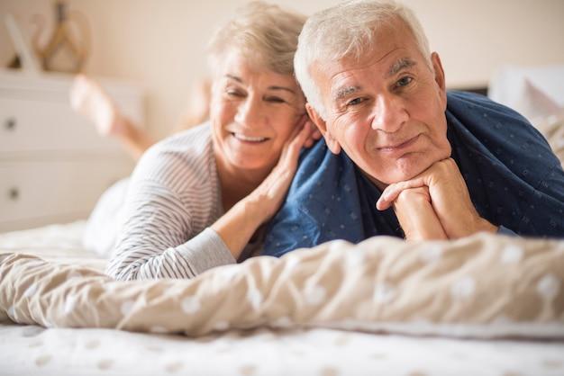 Glückliches älteres paar, das auf dem bett liegend ist