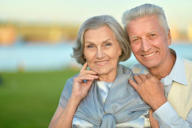 Glückliches älteres paar, das auf naturhintergrund umarmt