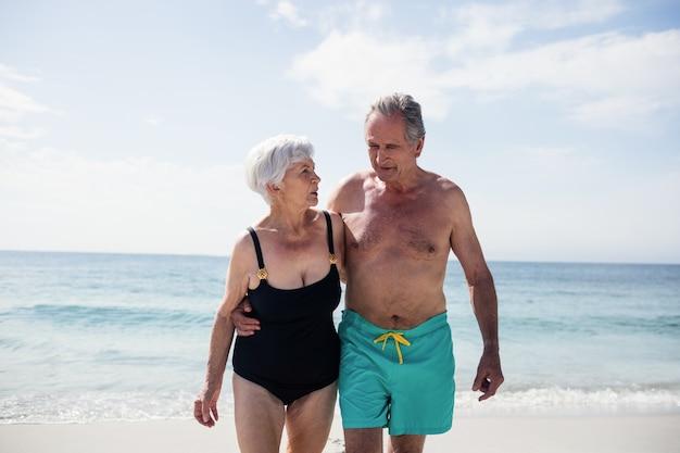 Glückliches älteres paar, das beim gehen am strand umarmt