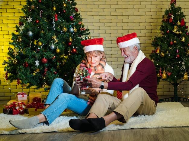 Glückliches älteres paar, das derzeit nach innen schaut, öffnete weihnachtsgeschenkbox zu hause. geschmückter weihnachtsbaum im wohnzimmer. romantischer winterurlaub.