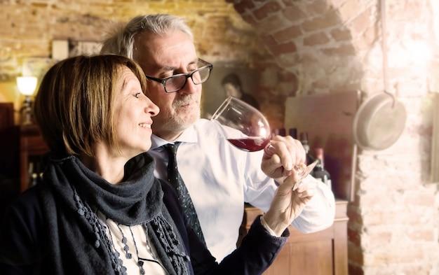 Glückliches älteres paar, das ein weinglas trinkend