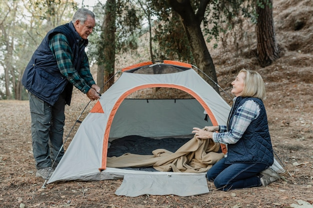 Glückliches älteres paar, das ein zelt im wald aufbaut