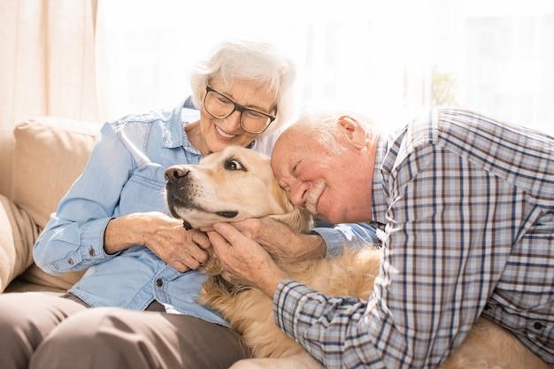 Glückliches älteres paar, das hund umarmt