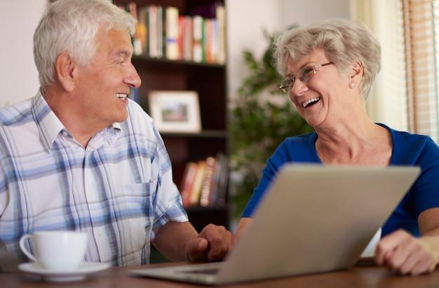 Glückliches älteres paar, das ihren laptop benutzt