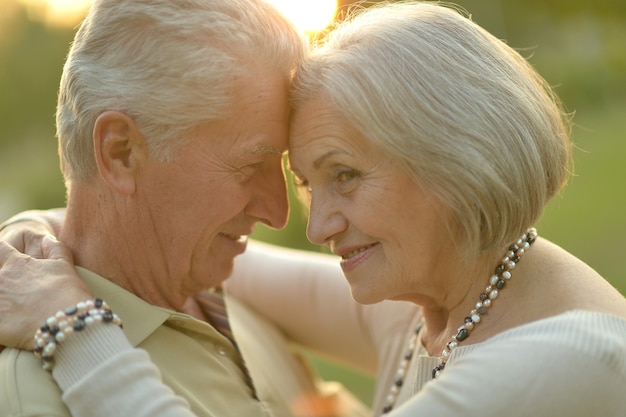Glückliches älteres paar, das im herbstpark steht