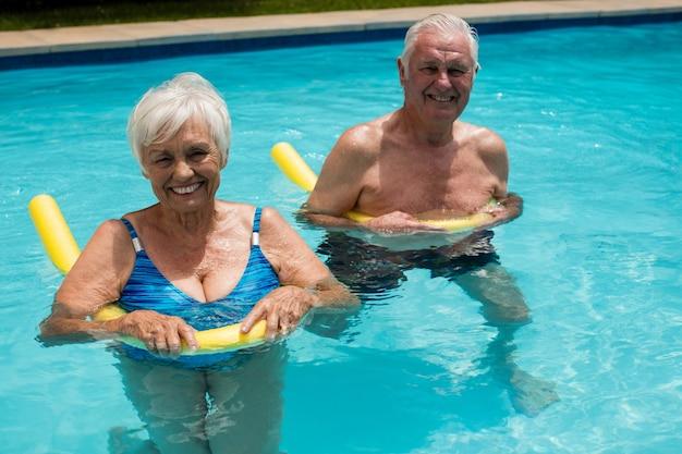 Glückliches älteres paar, das im pool mit aufblasbaren schläuchen schwimmt