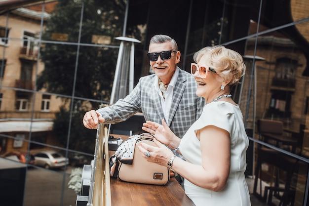 Glückliches älteres paar, das in der sommerterrasse auf modernem café lächelt. schöner tag