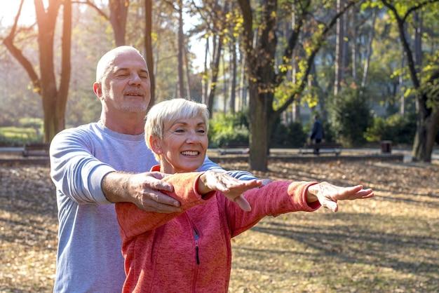 Glückliches älteres paar, das in einem park trainiert