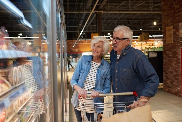 Glückliches älteres paar, das lebensmittel-sopping genießt