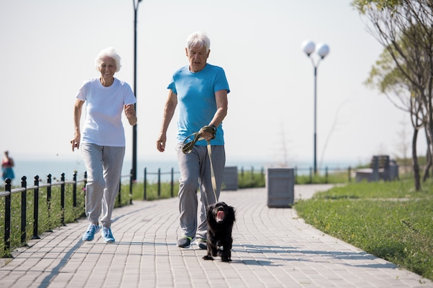 Glückliches älteres paar, das mit haustier-hund läuft