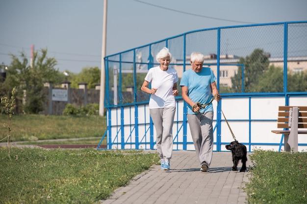 Glückliches älteres paar, das mit hund läuft