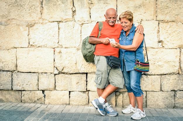 Glückliches älteres paar, das spaß mit einem modernen smartphone hat
