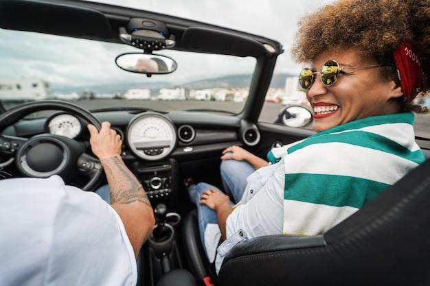 Glückliches älteres paar, das während der sommerferien spaß im cabrio-auto hat - fokus auf frauengesicht