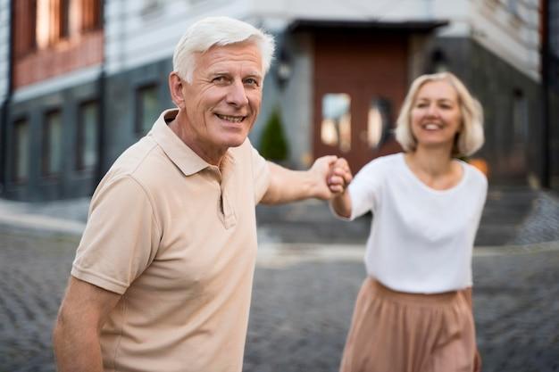 Glückliches älteres paar draußen in der stadt, das spaß hat