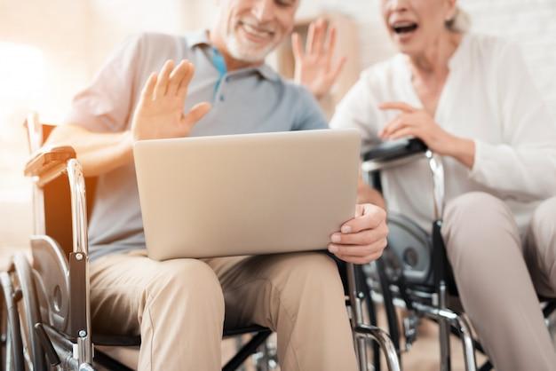 Glückliches älteres paar in den rollstühlen betrachtet laptopschirm.